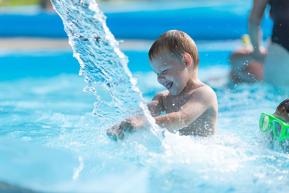 A young boy playing in a pool with a big splash of water